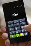 Hand, die 999 am Handy wählt Stockfotos