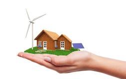 Hand, die Haus mit erneuerbarer Energie hält Stockfoto