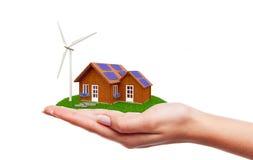 Hand, die Haus mit Windkraftanlage hält Lizenzfreie Stockbilder