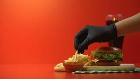 Hand die heerlijke frieten met saus, smakelijk maar ongezond snel voedsel nemen stock videobeelden