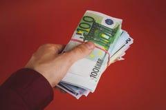 Hand, die heraus einen Stapel Geld auf einem roten Hintergrund hält lizenzfreie stockbilder