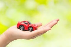 Hand die het model van auto op groene achtergrond houden Stock Fotografie