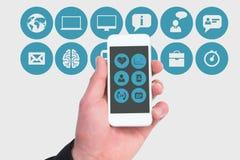 hand die het scherm van een smartphone tonen tegen de mobiele achtergrond van toepassingenpictogrammen stock foto
