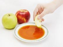 Hand die het stuk van appel in honing onderdompelt Stock Foto's