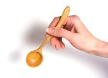 Hand die houten lepel houdt Stock Afbeeldingen