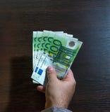 Hand, die hundert Eurorechnungen hält Stockfoto