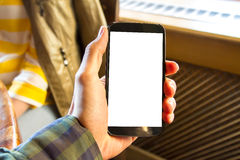 Hand, die intelligentes Telefon im Café hält Lizenzfreie Stockbilder