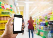 Hand, die intelligentes Telefon im Einkaufszentrum hält Stockfoto