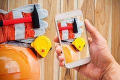 Hand, die intelligentes Telefon mit Triebschutzausrüstung hält lizenzfreie stockfotografie