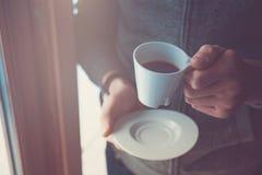 Hand, die Kaffeetasse hält Lizenzfreie Stockfotografie