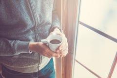 Hand, die Kaffeetasse hält Stockbilder