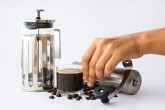 Hand, die Kaffeetasse und Franzosepresse hält Stockbilder