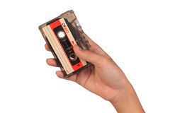 Hand, die Kassette lokalisiert auf weißem Hintergrund hält lizenzfreie stockfotos