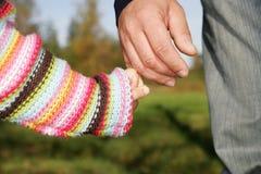 Hand, die Kindervaterabbinden hält Stockfotos