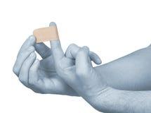 Hand, die klebenden Verband auf Mannfinger setzt. Lizenzfreies Stockfoto