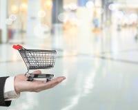 Hand die klein 3D leeg boodschappenwagentje houden Stock Afbeelding