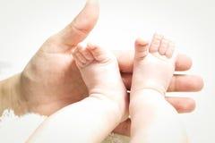 Hand, die kleine Füße hält Stockfotografie