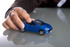 Hand, die kleines blaues Auto anhält Stockbild