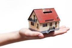 Hand, die kleines Miniaturhaus anhält Lizenzfreie Stockfotografie