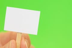 Hand, die kleines Zeichen auf Grün mit Exemplar-Platz anhält Lizenzfreies Stockbild