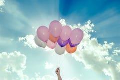 Hand die kleurrijke ballons op blauwe hemelachtergrond houden Stock Foto