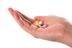 Hand die kleurrijke pillen houdt Stock Foto's