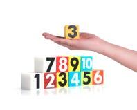 Hand die kleurrijke plastic aantallen op witte achtergrond, No1 houden Royalty-vrije Stock Foto's