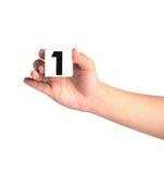 Hand die kleurrijke plastic aantallen op witte achtergrond, No1 houden Stock Fotografie
