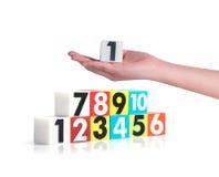 Hand die kleurrijke plastic aantallen op witte achtergrond, No1 houden Royalty-vrije Stock Foto
