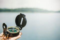 Hand, die Kompass über Naturhintergrund hält Lizenzfreie Stockfotografie