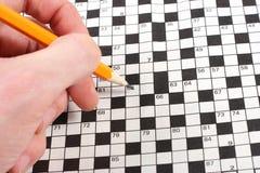 Hand, die Kreuzworträtsel tut Stockfotografie