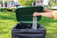 Hand die lege plastic fles werpen in het afval Royalty-vrije Stock Fotografie