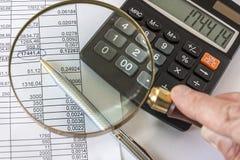 Hand, die Lupe zur Prüfung des Geschäftsdokumentes hält Lizenzfreies Stockbild