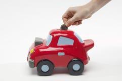 Hand, die Münze in Toy Car einfügt Stockfotografie