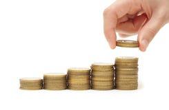 Hand, die Münze zum Geldtreppenhaus setzt Stockbilder