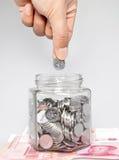 Hand, die Münzen in ein Glasglas einsetzt Lizenzfreies Stockfoto