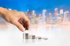 Hand, die Münzen gegen Stadtbildhintergrund hält Stockfotos
