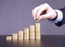 Hand, die Münzen stapelt Lizenzfreie Stockbilder