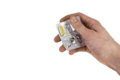 Hand die medische drugs houden - het volledige zilveren pamflet van witte pillen in gemeenschappelijke tabletten vormt, geïsoleer Stock Fotografie