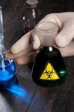 Hand, die medizinisches Rohr mit Symbol Biohazard hält Stockfotografie