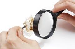 Hand die meer magnifier analyserend een zegel houdt stock afbeelding