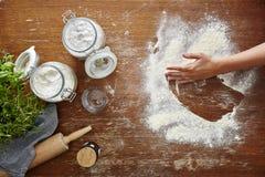 Hand, die Mehl auf atmosphärischer Küche des Holztischs abwischt Stockbild