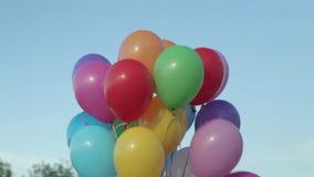 Hand, die mehrfarbige Ballone anhält stock video footage