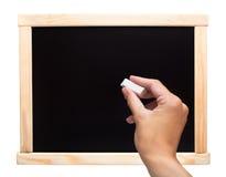 Hand die met krijt op een bord schrijven Stock Foto