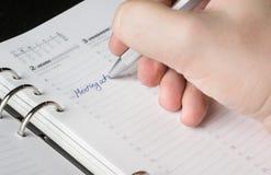 Hand die met zilveren pen op open agenda schrijven Royalty-vrije Stock Fotografie