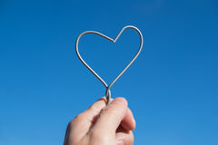 Hand die metaal te houden wordt misvormd om hartvorm te worden royalty-vrije stock foto's