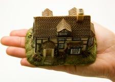 Hand, die Miniatur des Hauses anhält Stockbilder