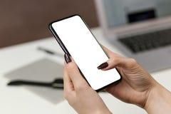 Hand die mobiele slimme telefoon met het lege scherm houdt stock fotografie