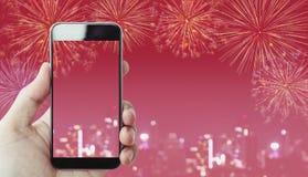 Hand die mobiele slimme telefoon, roze achtergrond met vuurwerk en Bokeh-licht houden Stock Afbeeldingen