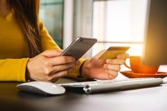 Hand die mobiele telefoon met creditcard online bankwezen olding stock foto
